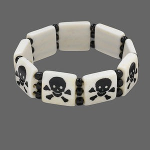 bracelet, stretch, bone (dyed) and glass, white and black, 4mm round and 16x16mm flat square with skull and crossbones design, 6-1/2 inches. sold individually.