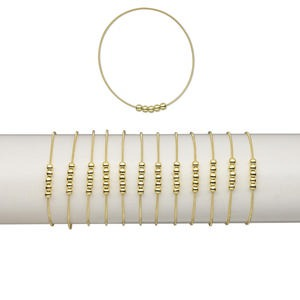 bracelet, stretch, plastic and brass, metallic gold, coil with 4.5mm round, 7 inches. sold per pkg of 12.
